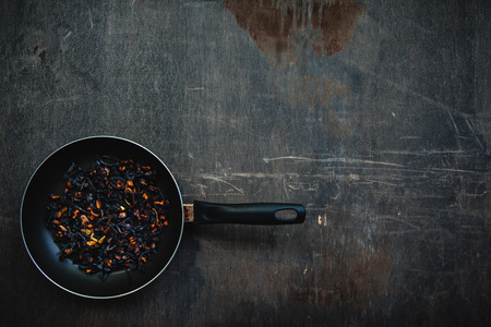 The failure on kitchen: burnt charred vegetables. Frying pan with refried black onion and overcooked orange carrots. Coocking fail concept background with copy space.