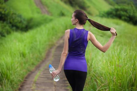 Slim girl in tight sportswear with bottle of water standing outdoors among green grass summer nature, middle back view.