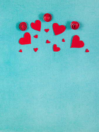 Overhead flat lay saint valentine day background. Handmade red hearts and flowers cut out of paper on blue textured background.