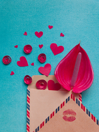 Overhead flat lay valentine day background. Red paper hearts and flowers handmade, kraft envelope letters with kiss print on blue texturred background. Bright inspiration for holiday of love.