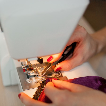 Female hands on sewing machine. Process of silk lingerie making. Close up of seamstress work. Stock Photo