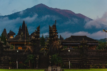 Balinese sacred mountain Agung colored in pink by sunset light. Main Bali temple Pura Besakih at the foot of the volcano Agung.