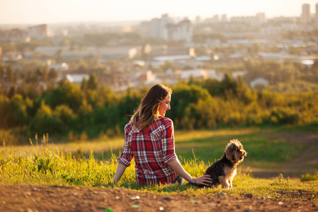 Young woman back in a red plaid shirt with her pet Yorkshire terrier sitting on the grass in a park. Friends looking at the city