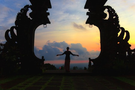 Silhouette of woman full length with arms wide open at the balinese traditional gates at the top of Pura Besakih at sunset.