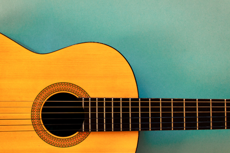 Acoustic classic guitar on blue background. Simple musical instrument with copy space