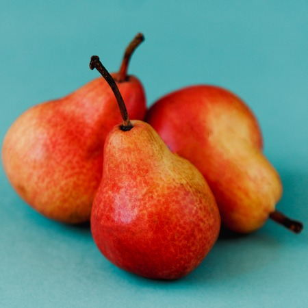 Three bright red williams pears on turquoise background Stock Photo - 100311825
