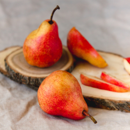 Bright red williams pears on linen wrimkled textile background. Ripe fruit in pastel colors.