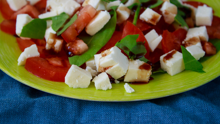Healthy vegetarian salad of red tomatoes, white cheese and fresh greens, seasoned with pomegranate sauce.