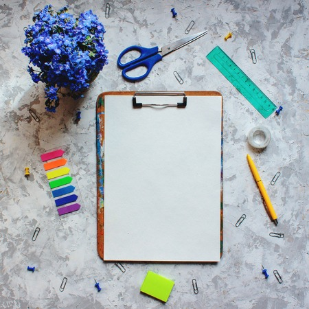 Stationery flat lay of white sheet of paper, colorful stickers and flowers. Workspace with empty page ready to write Standard-Bild