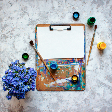Flat lay of wooden clipboard with white sheet of paper, acrylic paints and brushes Standard-Bild