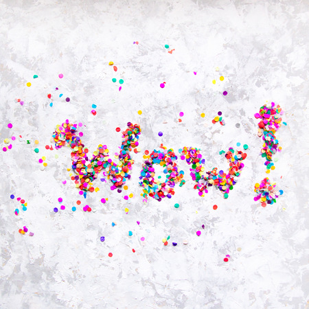 Word Wow! made of colorful confetti on white textured background.