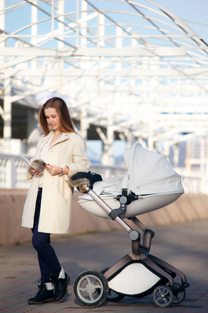 A young mother in a white coat walks along the seafront with a child in a stylish stroller. Concept of active motherhood.