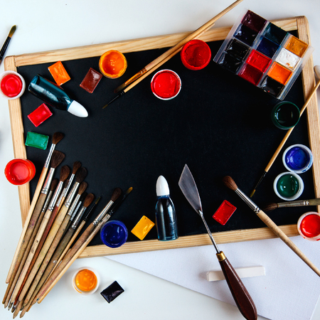 Drawing accessories, paints and brushes lie on an empty black chalkboard. The concept of creativity and painting. Overhead still life with copy space. Stock Photo