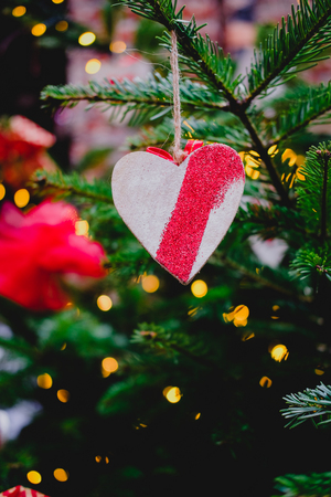 Wooden decorations in shape of heart hanging on a pine branch on Christmas tree. Romantic holiday concept.