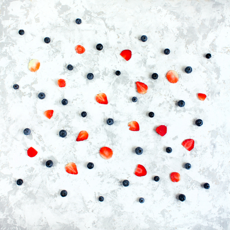Minimalistic flat lay pattern of fresh berries - blueberry and strawberry on white textured background.