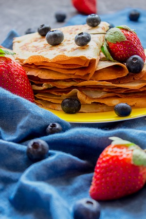 Side view stack of thin pancakesfolded in triangles and decorated with fresh strawberries and blueberries. The concept of Russian holiday Maslenitsa, Shrovetide Stok Fotoğraf