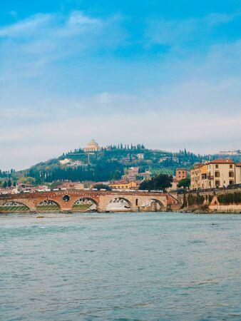 Roman arch bridge over Adige River in Verona. Historical center of European city. Romantic sightseeng trip to Italy 写真素材