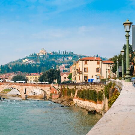 Roman arch bridge over Adige River in Verona. Historical center of European city. Romantic sightseeng trip to Italy Stock Photo