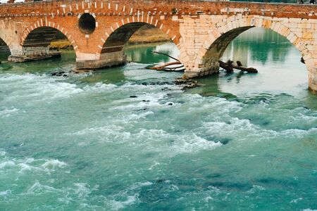 Roman arch bridge over Adige River in Verona. Historical center of European city. Romantic sightseeng trip to Italy. Stock Photo
