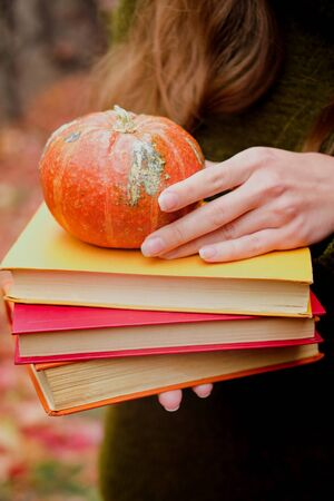Female hands holding a stack of three vintage paper books and small pumpkin among colorful ivy in autumn Stok Fotoğraf