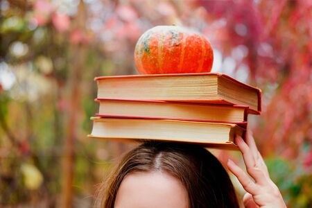 Stack of three vintage paper books and a small cute pumpkin on female head. What to read in autumn concept.