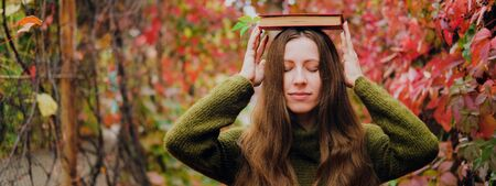 Girl with long hair holding a book on head among colorful ivy in autumn