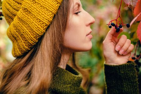 Girl in mustard yellow knit hat and marsh green wool sweater walking among colorful ivy in autumn Archivio Fotografico - 129472189