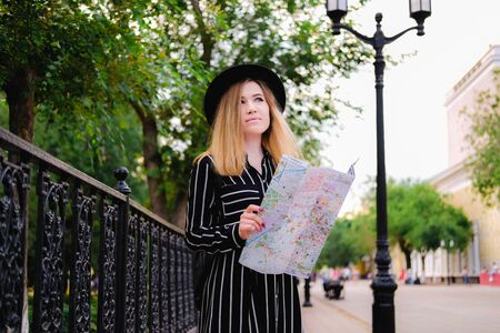 Blonde girl in black hat walking on the street. Woman looks at paper city map. Solo traveling concept.
