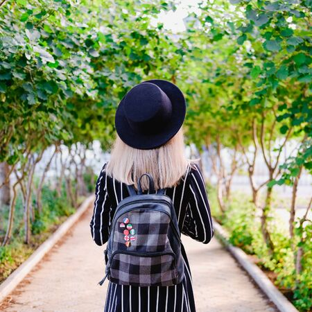 Blonde girl in black hat with backpack walking along the alley in the green garden. Female solo travel concept Banque d'images - 129472343