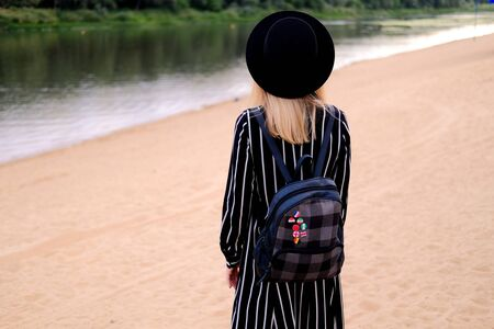 Blonde girl in black hat with backpack walking on the street. City traveling alone concept.