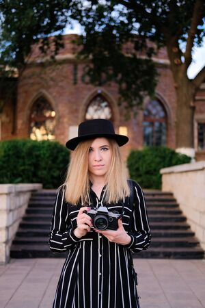 Blonde girl in black hat taking pictures with retro design camera on background of historic building. City traveling alone concept.