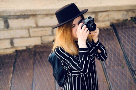 Blonde girl in black hat with backpack taking pictures with retro style camera. City traveling alone concept. 版權商用圖片