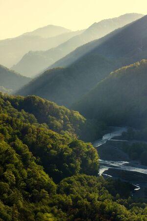 Sonnenuntergang am Kaukasus im Sommer. Grünes Tal mit Fluss. Tonalperspektivische Komposition. Schönes Naturkonzept.