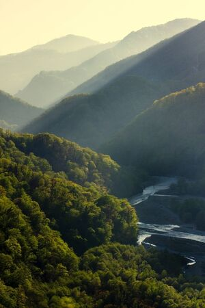 Sunset at Caucasus mountains in summer. Green valley with river. Tonal perspective composition. Beautiful nature concept. Stockfoto - 129474155