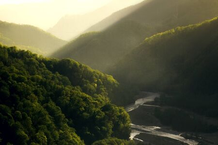 Sunset at Caucasus mountains in summer. Green valley with river. Tonal perspective composition. Beautiful nature concept.