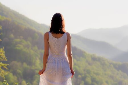 Girl in white dress standing back on the top of Caucasus mountain with a scenery view to sunset at green valley. Female travel nature concept. Stockfoto - 129474166