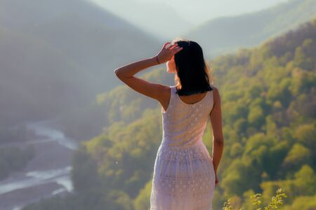 Girl in white dress standing back on the top of Caucasus mountain with a scenery view to sunset at green valley with river. Female travel nature concept. 版權商用圖片