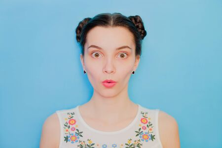 Funny cute girl on a blue studio background. Bright emotional female portrait. Surprised face with open mouth. 版權商用圖片