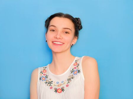 Funny cute girl on a blue studio background. Bright emotional female portrait. Happy smiling freamy face