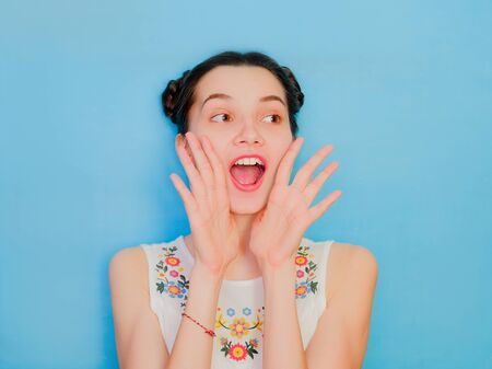 Funny cute girl on a blue studio background. Bright emotional female portrait. Happy screaming face. Hands up as tube.