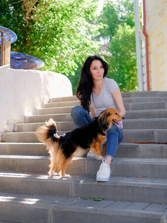 Brunette woman is sitting on stairs with her dog. Funny spaniel mutt in summer city. 版權商用圖片