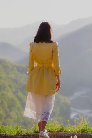 Girl in white dress standing back on the top of Caucasus mountain with a scenery view to sunset at green valley. Female travel nature concept. Stockfoto - 129472333