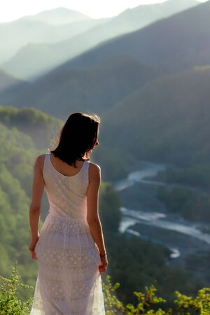 Girl in white dress standing back on the top of Caucasus mountain with a scenery view to sunset at green valley with river. Female travel nature concept. Stockfoto - 129472337