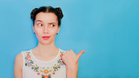 Funny cute girl on a blue studio background. Bright emotional female portrait. Woman raises one eyebrow. Finger points to copy space