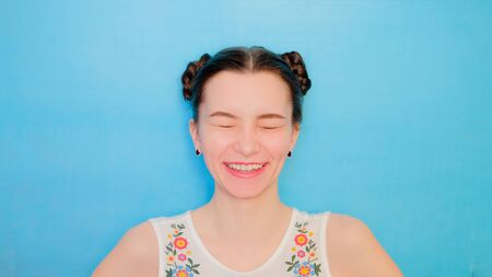 Funny cute girl on a blue studio background. Bright emotional female portrait. Woman blinks and laughs.