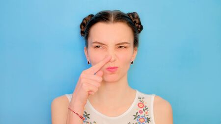 Funny cute girl on a blue studio background. Bright emotional female portrait. Woman wrinkles nose from bad smell.