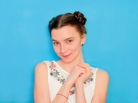 Funny cute girl on a blue studio background. Bright emotional female portrait. Woman is touched and flattered. 版權商用圖片
