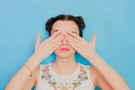 Funny cute girl on a blue studio background. Bright emotional female portrait. Woman covering eyes by hands. Sees no evil three monkeys concept 版權商用圖片