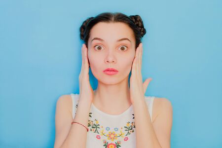 Funny cute girl on a blue studio background. Bright emotional female portrait. Woman covering ears by hands. Hears no evil three monkeys concept 版權商用圖片