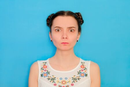 Funny cute girl on a blue studio background. Bright emotional female portrait.